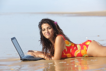 young woman using laptop on wet sand at beach photo