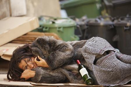 alcoholismo: mujer joven vagabundo tumbado con la botella de vino en bin