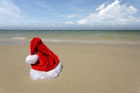 vivid santa hat standing on tropical beach under sunlight photo