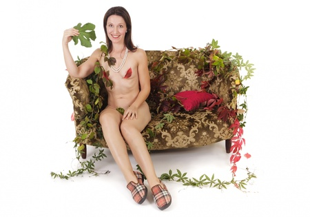 naked kitsch woman sit on retro couch using fig tree leaf as fan Stock Photo - 10995191