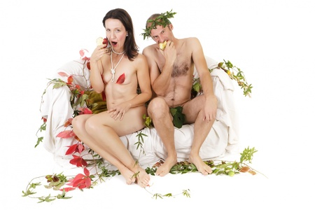 adam eve: nude funny couple sitting on couch eating red apple Stock Photo