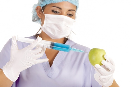 female researcher injecting liquid in green apple photo