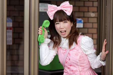 japanese girl in sweet lolita cosplay style in public phone, Tokyo photo