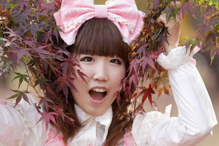 japanese girl in sweet lolita cosplay style in red fall mapple,Tokyo photo