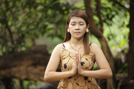 young thai woman meditation in tropical forest photo