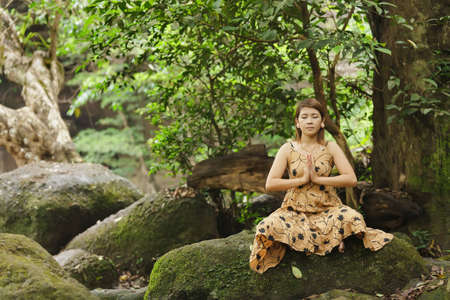 young asian woman meditating in wild forest, thailand photo