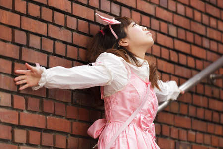 lolita: stressed japanese lolita cosplay leaning against brick wall on stairs