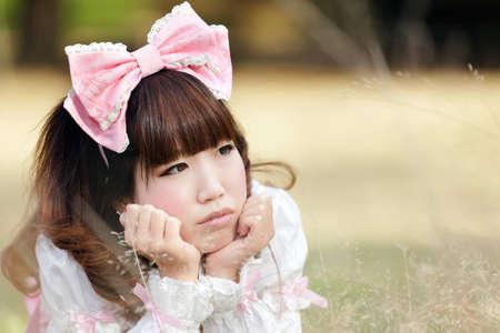 lolita: japanese woman in sweet lolita cosplay lying in meadow, tokyo Stock Photo