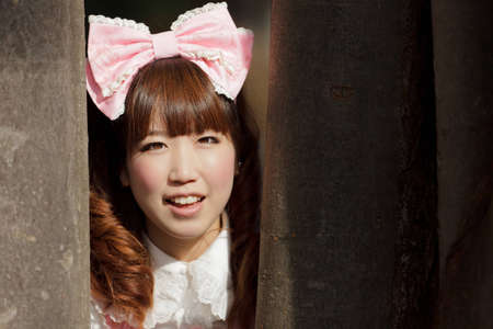 lolita: japanese woman in sweet lolita cosplay  hiding in forest