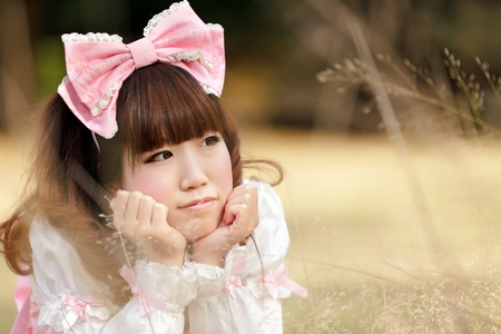 japanese woman in sweet lolita cosplay lying in meadow, tokyo photo