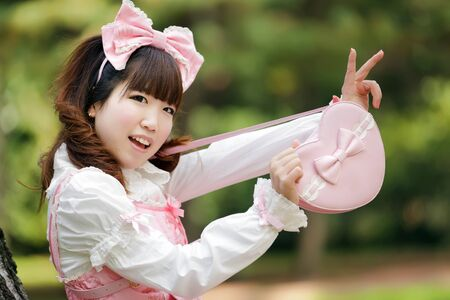 lolita: japanese woman in sweet lolita cosplay showing heart bag Stock Photo