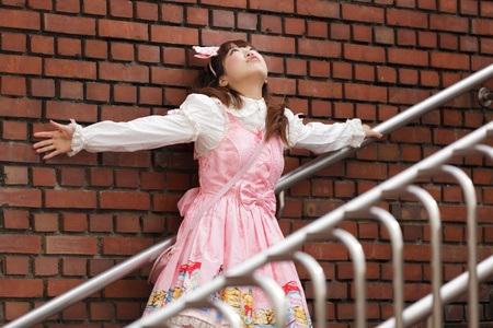japanese lolita cosplay leaning against brick wall on stairs photo