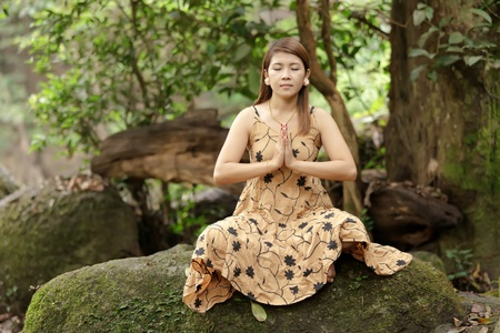 young woman praying meditation in wild nature, thailand photo