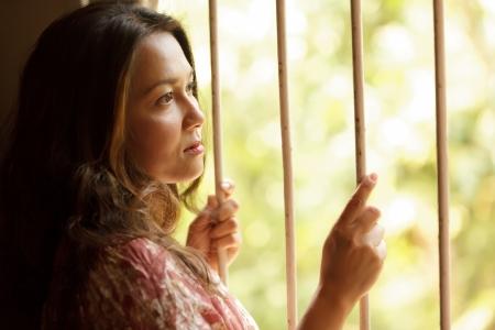 mirada triste: mujer triste nostalgia la celebración de las barras de la ventana y mirando hacia afuera