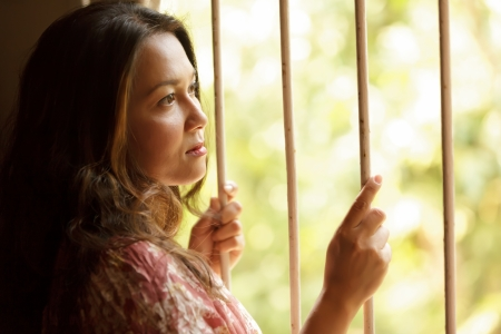 woman prison: nostalgic sad woman holding window bars and looking outside