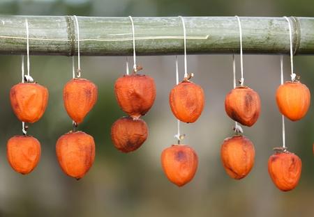 gedroogde kaki fruit opknoping van een bamboe stok, Japan