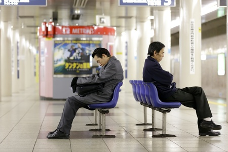 TOKYO - NOVEMBER 30: worker men waiting subway early morning and falling asleep on chairs on November 30, 2011 in Tokyo, Japan.