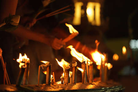 candles burning during buddhist ceremony in thai temple, Chiang Mai, Thailand