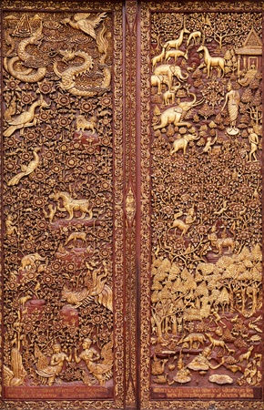 wooden carving in buddhist temple door, Thailand photo