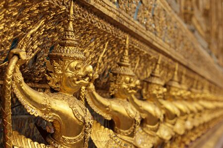 perspective view of golden religious statue in wat phra kaeo temple, Bangkok, Thailand, shallow depth of field photo