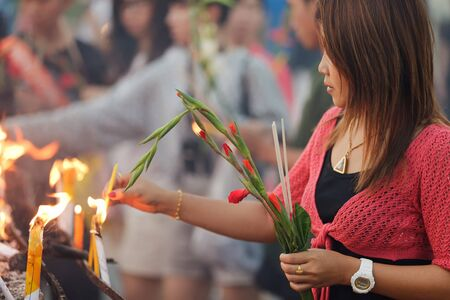 buddhist woman holding gladiolus flower and  igniting incense stick in thai Temple