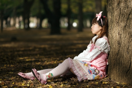 sad japanese lolita leaning against tree in park photo