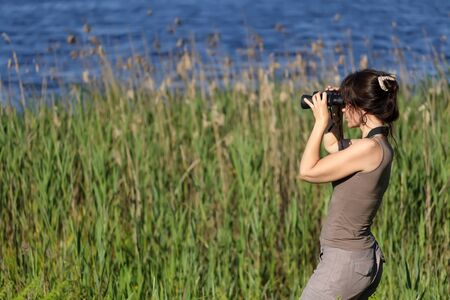 woman watching wildlife with binoculars in swamp area photo