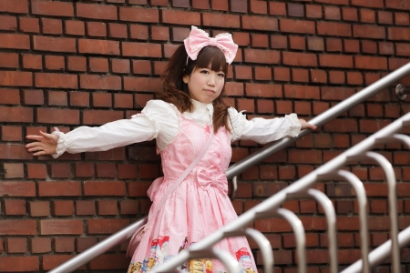 lolita: japanese lolita cosplay leaning against brick wall on stairs