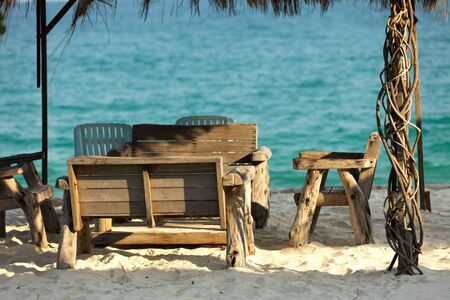 wooden chairs and table in tropical beach restaurant, thailand photo