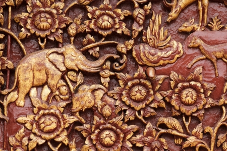 religious wooden carving detail of buddhist temple door, Thailand photo