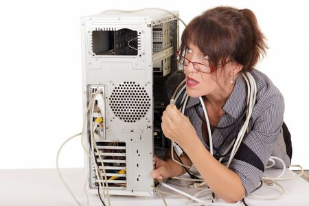 confuse woman trying to plug a cable in computer photo