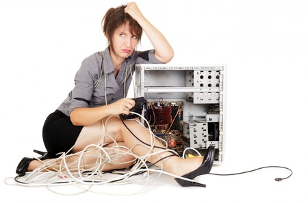 tangled: worried woman sulking with broken computer Stock Photo