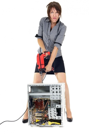 broken computer: business woman destroying computer with electric drill