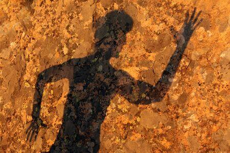 woman shadow: woman shadow on granite rock under warm sunset light Stock Photo