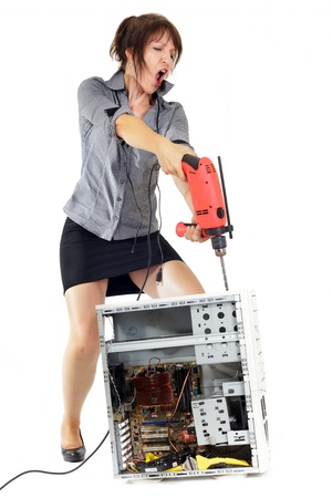 furious business woman piercing computer with electric drill photo