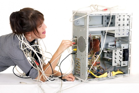 business woman tangled with cables trying to plug  wire on computer photo