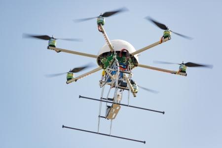 uav drone hexarotor flying in blue sky Stock Photo