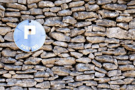 advert: old stone wall with parking sign advert