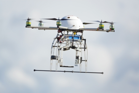UAV robot drone vliegen in bewolkte hemel Stockfoto