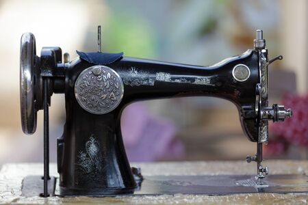 Old traditional metallic sewing machine with many asian decorations, Thailand photo