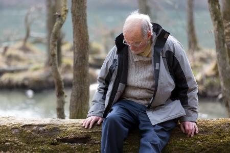 Nadenkend senior man zittend op de boomstam in de natuur Stockfoto