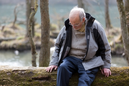 bowed head: Pensive senior man sitting on tree trunk in nature