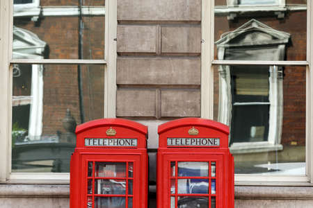 Traditional London telephone boxes with building architecture reflection