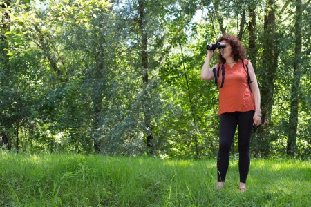 Middle aged woman observing wildlife with binoculars photo