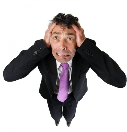 unusual angle: High angle full length portrait of an expressive anxious businessman tearing at his hair isolated on white