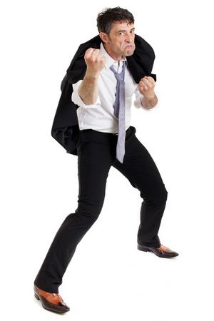 jambes �cart�es: Bellig�rant homme en col�re ramasser un combat permanent avec sa veste sur son �paule et jambes �cart�es renfrogn� et mena�ant du poing Banque d'images