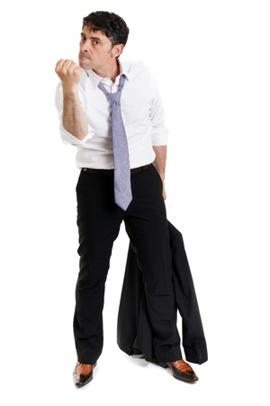 irate: Enraged business man with his suit jacket in his hand making a threatening gesture with his fist and giving a belligerent look isolated on white