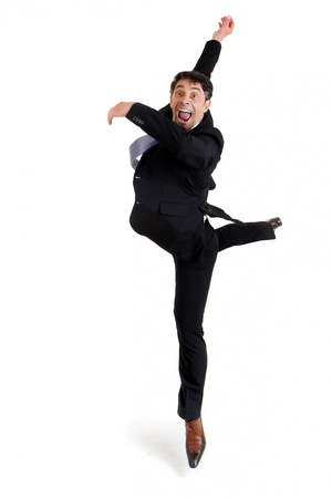 Fun portrait of an excited agile businessman in smart shoes and a suit performing ballet doing a pirouette, isolated on white photo