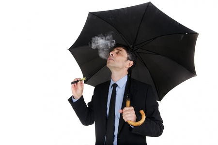 Man holding umbrella and smoking electronic cigarette Stock Photo - 20537536