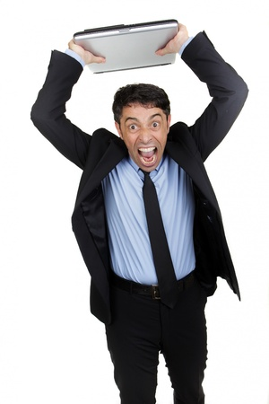 provocation: Angry businessman yelling with a ferocious expression and open mouth standing with his arms raised throwing his laptop isolated on white